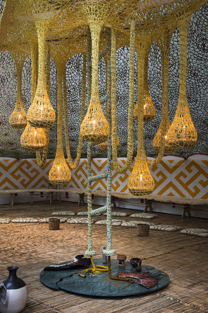 Ernesto Neto sculpture of yellow drooping nets with lights inside.